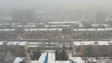 Aerial view of building roof covered with snow. Winter foggy cityscape background.