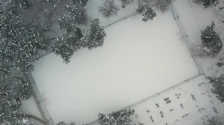 Aerial view of empty kids playground in the city park is covered with snow. Foggy winter day.