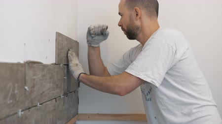 çini : Home improvement, renovation - construction worker tiler is tiling, ceramic tile wall adhesive, trowel with mortar