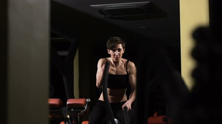 exercícios : CrossFit. Muscular woman exercising with rope in crossfit gym
