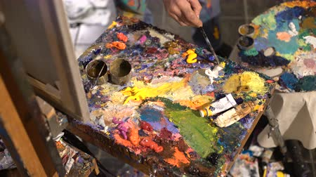 expressionism : Artist mixes oil paints on pallet with various colors