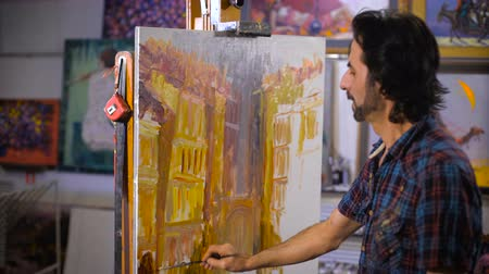 artistas : A male artist painting in his studio