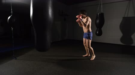 bokszoló : muscular handsome fighter giving a forceful forward kick during a practise round with a boxing bag. Stock mozgókép