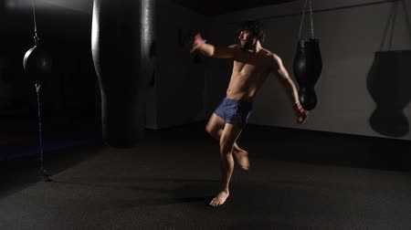sağlam : fury. muscular handsome fighter giving a forceful forward kick during a practise round with a boxing bag. Stok Video