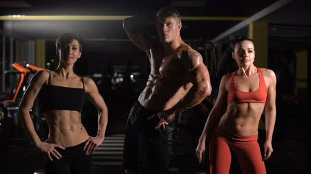 bicep : A small group of athletes posing with a fitness equipment Stock Footage