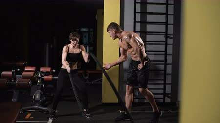 pulling rope : bodybuilder teaches exercise his girlfriend. Athletic young woman doing some crossfit exercises with a rope