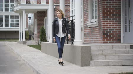 eski moda : Beautiful leggy blonde confident gait walking down the street. Black leather jacket,