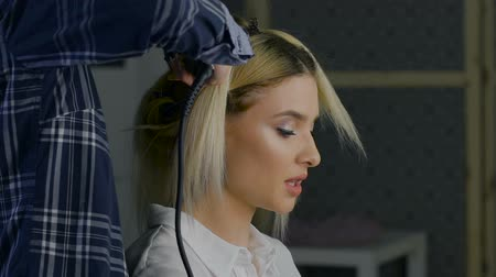 fryzjerstwo : in a beauty salon eccentric stylist makes professional styling for the girls. hairstyle for blonde