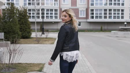 pózol : beautiful blonde walking on the sidewalk around the stylish home. She is a young
