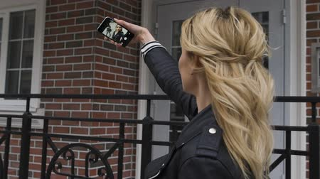 filmowanie : Side portrait of a beautiful blond girl using a smart phone to network, taking selfies pictures in a suburban home exterior, outdoors.