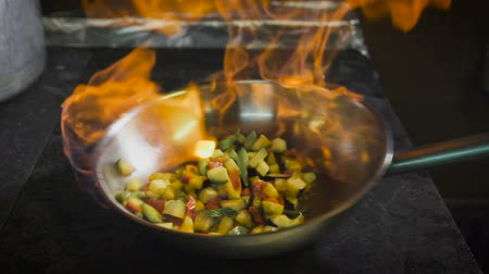 chef : Chef frying vegetables. Cognac is ignited in the pan. Open fire in the kitchen