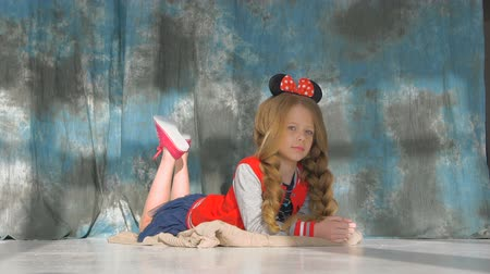 капелька : Little girl with long braids in a red jacket. Posing in the studio,