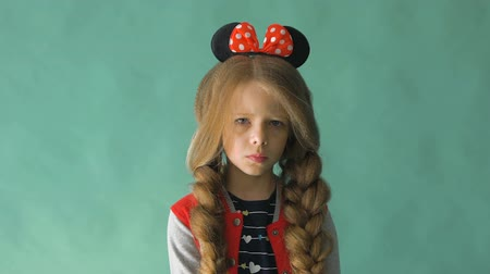 милый : Little girl with braids and a bow in her hair. Posing in the studio Стоковые видеозаписи