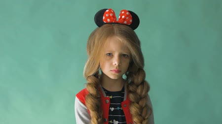 posando : Little girl with braids and a bow in her hair. Posing in the studio Stock Footage