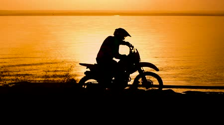 lovas : Off-road motorbike extreme cornering. Motorcyclist at sunset near the river. Extreme motocross bike, dirt from under the wheels.