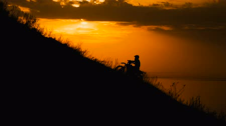 toprak : motocross rider storms obstacle. Climb up the hill on the road. Sunset painted the sky