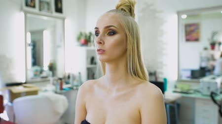 skin brown : fashion stylist, creating an image for the top model. She was prepared for a photo shoot or fashion show on the catwalk. Expressive makeup Stock Footage