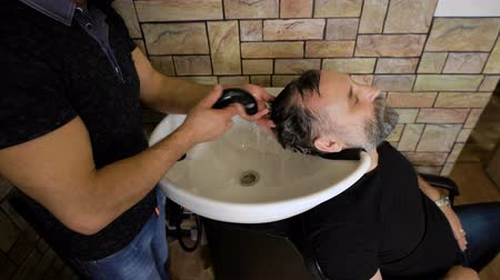 cabelos grisalhos : eccentric stylist washes head respectable men. Businessman visits to his barber, that would shear the beard. Vídeos