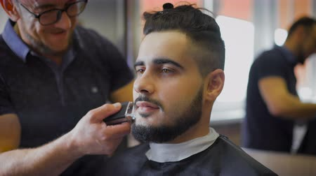 cutting up : Young, brave hipster in your favorite barber shop. Master engaged in his beard, uses a trimmer to shape according to the latest trends.
