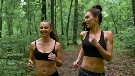 kocogó : fitness workout outdoors. Two slender brunette with long hair running through the woods and communicate. Stock mozgókép
