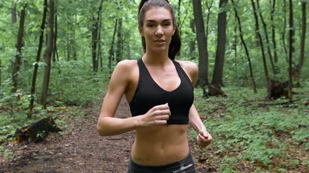 kocogó : fitness workout outdoors. Sport woman running through the woods. Shes in a good mood and a great figure. Deciduous forest after the rain.