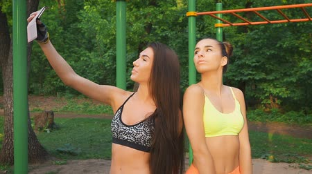 self made : Two girls make merry fitness selfie. Sports figures and good mood. Stock Footage