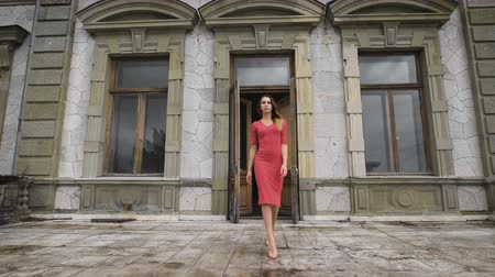 konak : Attractive girl in red dress goes on the balcony of an old manor.