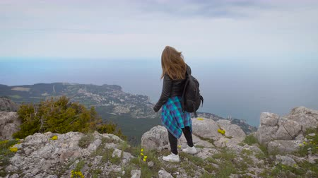 podróżnik : Woman traveler looks at the edge of the cliff on the sea bay of mountains in the background