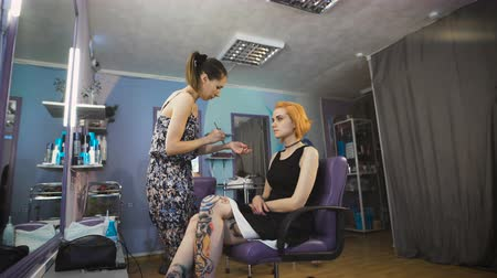 салон : Extravagant girl in a black dress and with the red color of hair in a beauty salon.