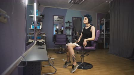 serseri : Punk girl with blue hair and tattooed legs in a beauty salon.