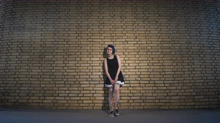 гот : Street youth movements and styles. Beautiful girl in a black dress on brick wall background.