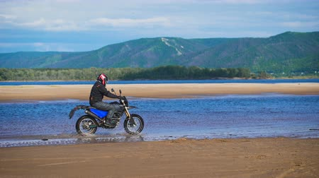 helmets : Extreme motorcyclist rides on sandy bank of the river.