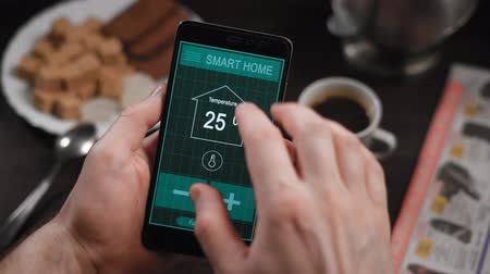 automatizálás : Smart home, application on the phone. A man manages various parameters of his home from a smartphone. Smart home technologies allow you to control lighting, temperature, security systems Stock mozgókép