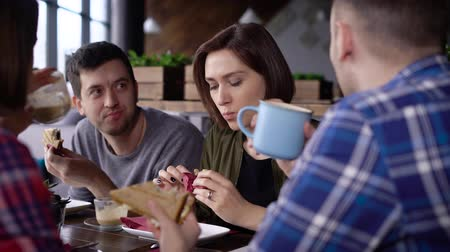 coffee time : Creative modernly dressed friends met at lunch time during the break. Girls and boys left the office to eat on a sandwich and drink coffee. Friends communicate on various topics in your favorite cafe. Stock Footage