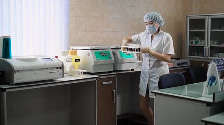 clínico : Female specialist turning on centrifuge. Female specialist in white uniform turning on centrifuge with blood specimen.