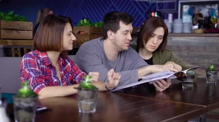 looking : Three smiling people sitting in cafe and choosing food and beverages looking at the menu attentively. Friends spending their time together at the restaurant and discussing their dining. Stock Footage