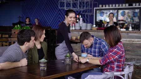 konuksever : Hospitable young waitress at the cafe bringing beverages in coloured mugs to the clients. Four friends sitting at the restaurant spending their free time together and getting their order. Stok Video