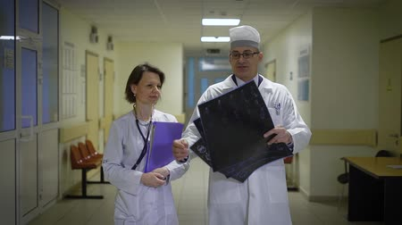 белый : Male and female doctors dressed in lab coats walking through the corridor of the ward and discussing roentgenograms. Professor of medicine in uniform is holding x-ray shots