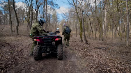 quadbike : Two athletes who wear protective helmets and clothes jump on the ATV and swiftly ride along the autumn forest