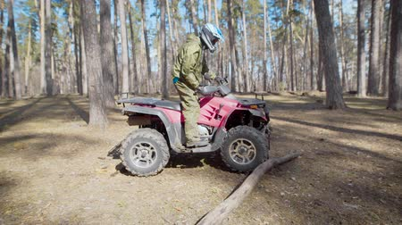 quadbike : A man in a protective helmet who rides on quad bike in the autumn forest crosses small barriers in the form of trees and branches that are on the road Stock Footage