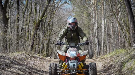 quadbike : A young man who rides a sports quad bike lifts the front wheels upwards by making a small jump, a person quickly rides a hill in the autumn forest