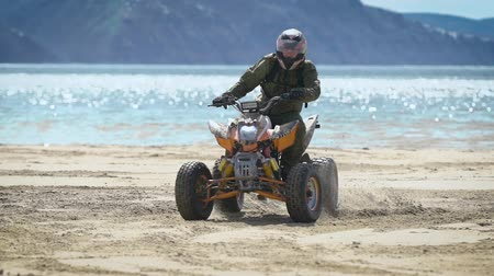 quadbike : A man with a helmet on his head rides along a sandy beach near the sea on a sport ATV, a person quickly turns the vehicle with a rudder on a vehicle Stock Footage
