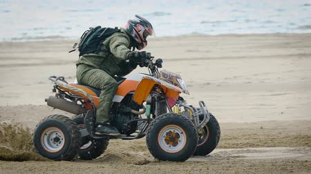 quadbike : An adult man performs a trick on a sports quad bike riding on a sandy beach, a person professionally manages an extreme country of transport