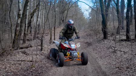 quadro : Autumn forest. The man in a special form on the ATV. The racer rides on the wood the racing ATV.