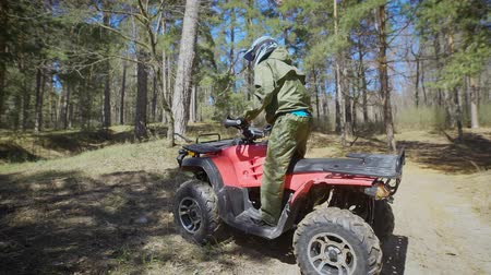 pétala : Autumn forest. The man in a special form on the ATV. The racer rides on the wood the racing quad bike. Stock Footage