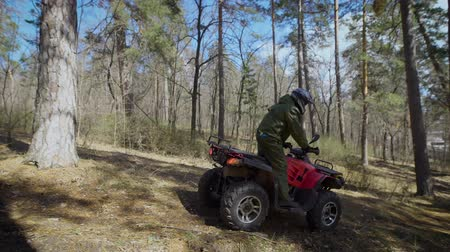 all ages : The racer in the forest. The man slowly rides the ATV on the autumn scaffold. In the forest its easiest to train on an ATV on off-road driving