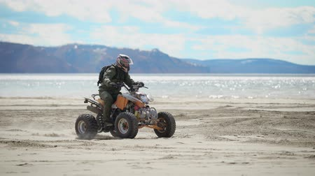 gimmick : River bank. Sunny weather on the beach. A man is riding an ATV on fine sand. The racer on the ATV carries out roundabouts.