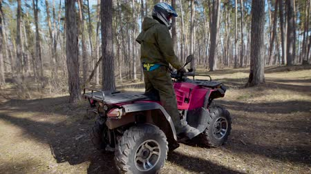 all ages : The racer in the wood. The man on the ATV. The man in a special form and a helmet quietly rides the ATV on forest roads.