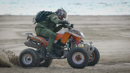 splint : River bank. The racer works the movements on the quad bike. The man on the ATV studies driving at sand.