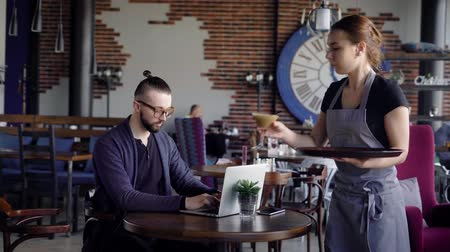 konuksever : Hospitable young waitress at the cafe is bringing glass of coffee to client. Young stylish man in casual clothes is sitting at the restaurant, spending free time and working with laptop.
